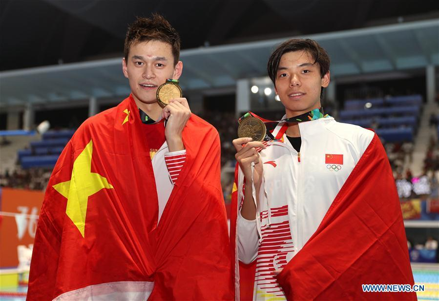 Gold medalist Sun Yang (L) of China and bronze medalist Ji Xinjie of China pose for pictures after the awarding ceremony of men\'s 1500m freestyle final of swimming at the 18th Asian Games in Jakarta, Indonesia, Aug. 24, 2018. (Xinhua/Fei Maohua)