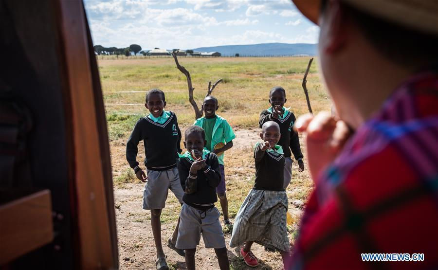 Children greet Chinese wildlife conservationist Zhuo Qiang (R) as he passes by in Maasai Mara, Kenya, July 6, 2018. The founder and Chairman of Mara Conservation Fund (MCF) Zhuo Qiang, a 45-year-old Chinese, has pioneered outstanding wildlife conservation projects in the world famous Maasai Mara ecosystem. Ol Kinyei is among the conservancies benefiting from his activities. Around it, he has built three lion proof boas preventing the wildlife conflict with the adjacent communities. He was officially adopted as a son of the Maasai\'s Ol Kinyei conservation group in 2015, owing to his unwavering friendship with the pastoralists. Zhuo\'s anti-poaching drives in the East African nation expresses the increasing collaboration between Kenyan and China in ending the killing of rhinos, elephants and lions. (Xinhua/Lyu Shuai)