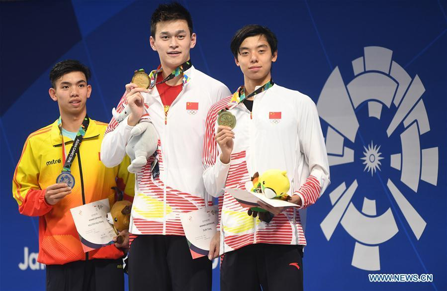 Gold medalist Sun Yang (C) of China and bronze medalist Ji Xinjie (R) of China attend the awarding ceremony of men\'s 1500m freestyle final of swimming at the 18th Asian Games in Jakarta, Indonesia, Aug. 24, 2018. (Xinhua/Pan Yulong)