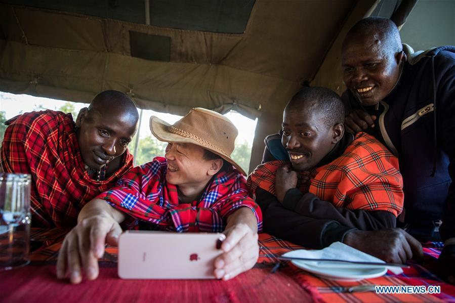 Chinese wildlife conservationist Zhuo Qiang (2nd L) watches a football match with locals at Ol Kinyei conservancy in Maasai Mara, Kenya, July 7, 2018. The founder and Chairman of Mara Conservation Fund (MCF) Zhuo Qiang, a 45-year-old Chinese, has pioneered outstanding wildlife conservation projects in the world famous Maasai Mara ecosystem. Ol Kinyei is among the conservancies benefiting from his activities. Around it, he has built three lion proof boas preventing the wildlife conflict with the adjacent communities. He was officially adopted as a son of the Maasai\'s Ol Kinyei conservation group in 2015, owing to his unwavering friendship with the pastoralists. Zhuo\'s anti-poaching drives in the East African nation expresses the increasing collaboration between Kenyan and China in ending the killing of rhinos, elephants and lions. (Xinhua/Lyu Shuai)
