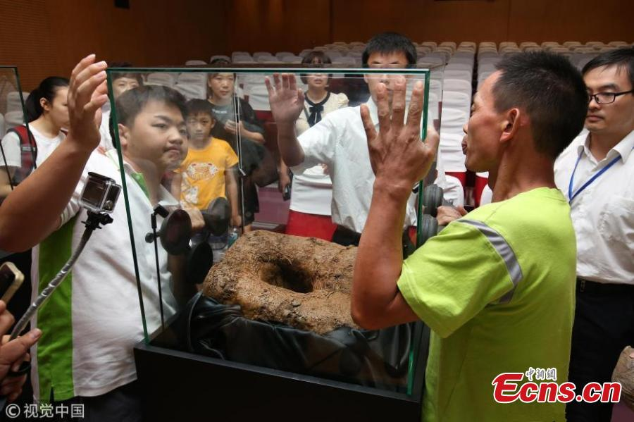 Visitors view a meteorite crater exhibited at a press conference held by Shanghai Planetarium in east China\'s Shanghai, Aug. 25, 2018. Shanghai Planetarium on Saturday announced plans to house meteorites recovered from a meteor fireball that happened over the sky in Jinghong City of southwest China\'s Yunnan Province in June. The planetarium, which is under construction, will be a branch of the Shanghai Science & Technology Museum. The museum staff have successfully recovered more than 500 pieces of meteorites, about 50 kg in total, said Lin Qing, deputy director in charge of the planetarium construction, at a press conference Saturday. (Photo/VCG)