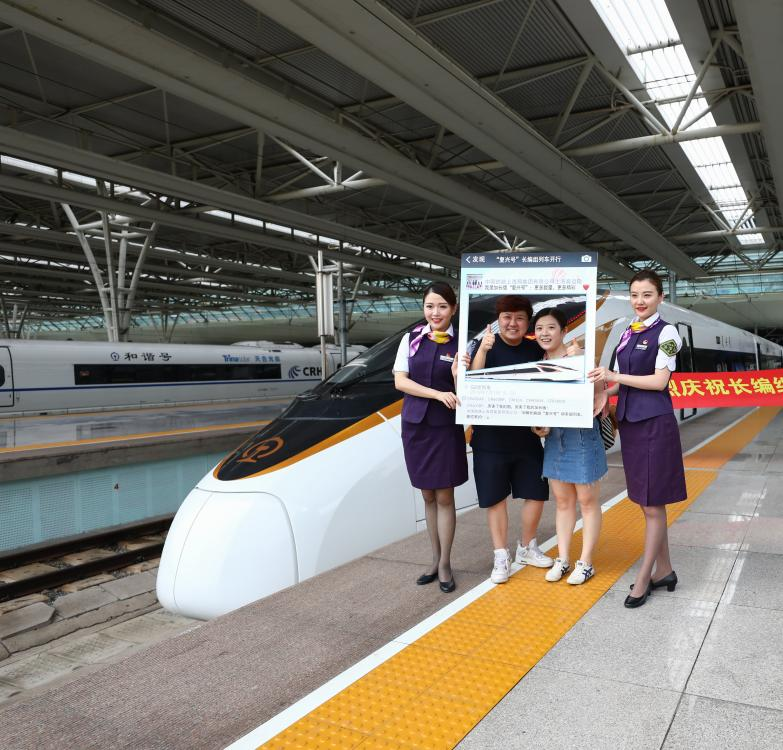 Present: Attendants of the Fuxing bullet train take photos with passengers before operation between Shanghai and Beijing. The speediest trip now takes four hours and 18 minutes. (Photo/Shine.cn)