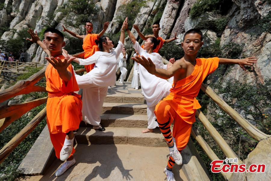 Yoga and kung fu enthusiasts perform in a cultural festival on Mount Song, home to the Shaolin Temple, in Dengfeng, Central China's Henan Province, Aug. 25, 2018. (Photo: China News Service/Wang Zhongju)