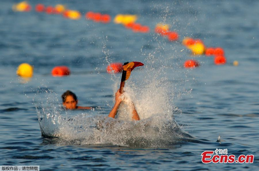 A competitor plunges into the sea while clutching the final flag after falling off the \