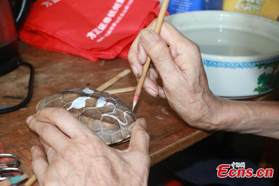 Wei Peikun, who hails from a family long-involved with Peking Opera, shows some of the typical masks he draws on turtle shells in Hangzhou City, East China's Zhejiang Province, Aug. 27, 2018. Wei, now in his eighties, said he started creating the intricate drawings 20 years ago in order to carry on the culture of the traditional form of Chinese opera, which combines music, vocal performance, dance and acrobats. (Photo: China News Service/Liu Peiqi)