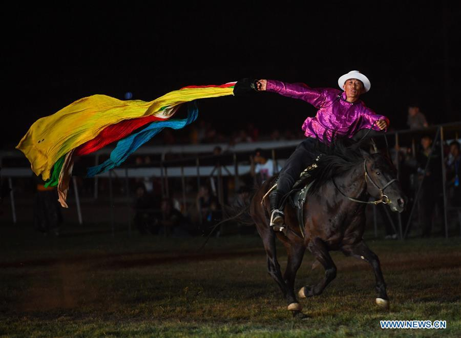 A performer collects hada (a piece of silk used as a greeting gift) on horse during the opening ceremony of a horse-themed art week in Hohhot, capital of north China\'s Inner Mongolia Autonomous Region, Aug. 27, 2018. Kicked off here on Monday, the art week will include art performances, beer and food festival, and equestrian performances. (Xinhua/Peng Yuan)