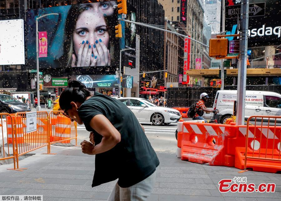 A woman reacts to a swarm of bees in Times Square in New York City, U.S., Aug. 28, 2018. The New York Police Department\'s bee keepers unit responded to the scene and safely removed the bees without incident. (Photo/Agencies)