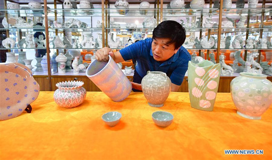 Chai Zhanzhu, the representative inheritor of Dangyangyu kiln Jiao Tai pottery firing, observes a pottery at Dangyangyu Village of Xiuwu County in Jiaozuo, central China\'s Henan Province, Aug, 27, 2018. The Dangyangyu kiln Jiao Tai pottery firing is a handicraft that was listed as a national intangible cultural heritage in 2014. The Jiao Tai pottery is made by blending clays of differing colours together, creating distinctive veined or mottled patterns. The handicraft is therefore recognized as \