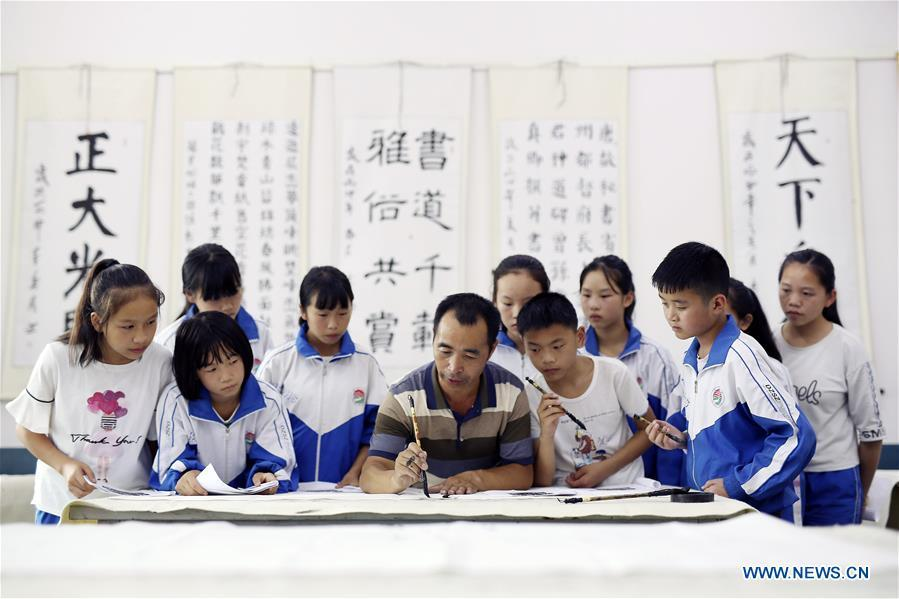 A teacher demonstrates Chinese calligraphy skills for students during an activity at the first lesson of the new term at the Danzhai No. 3 Middle School in Danzhai County, southwest China\'s Guizhou Province, Aug. 29, 2018. Schools in China prepared many activities for students to greet the new semester after summer vacation. (Xinhua/Huang Xiaohai)