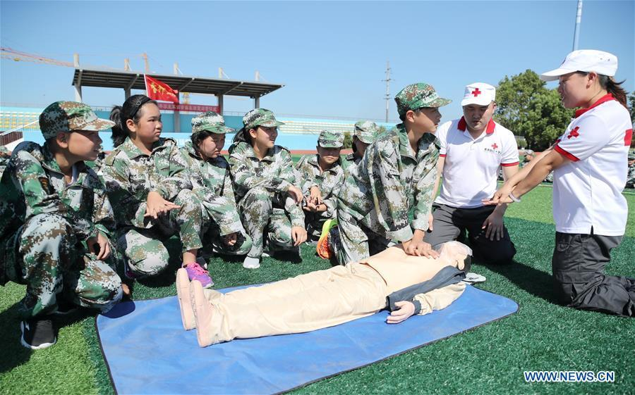 Newly-enrolled middle school students learn to do first aid during military training practice at Xinshi Middle School in Xinshi Town of Huzhou City, east China\'s Zhejiang Province, Aug. 29, 2018. Schools in China prepared many activities for students to greet the new semester after summer vacation. (Xinhua/Xie Shangguo)