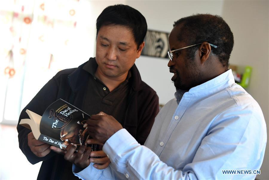 Diarra introduces an English book about the traditional Chinese medicine to his friend in Kunming, southwest China\'s Yunnan Province, Aug. 28, 2018.(Xinhua/Lin Yiguang)
