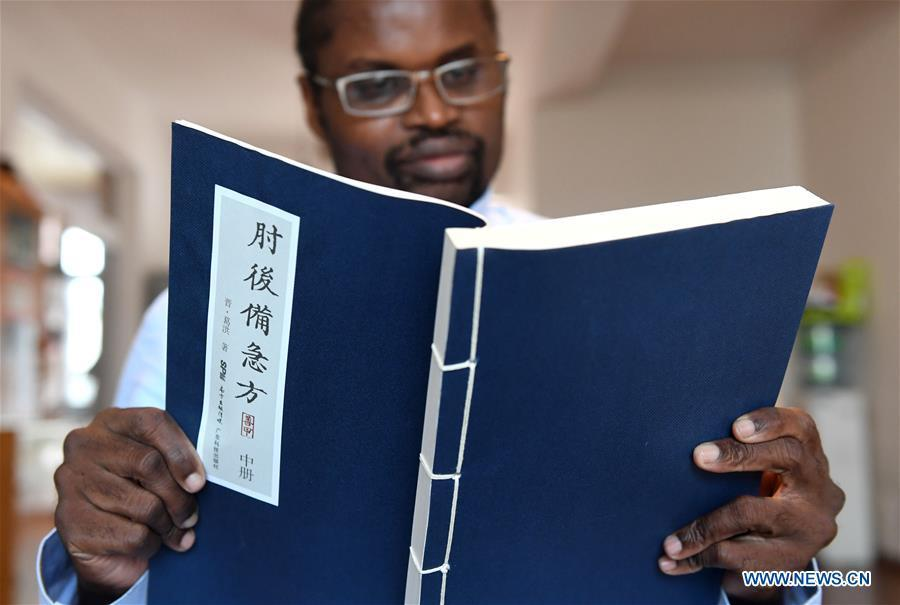 Diarra reads a book of traditional Chinese medicine at home in Kunming, southwest China\'s Yunnan Province, Aug. 28, 2018. (Xinhua/Lin Yiguang)