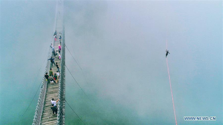 People watch a man walking on a webbing during a slacklining competition held in Shenxianju scenic spot in Xianju County, east China\'s Zhejiang Province, Aug. 25, 2018. (Xinhua/Zhu Cheng)