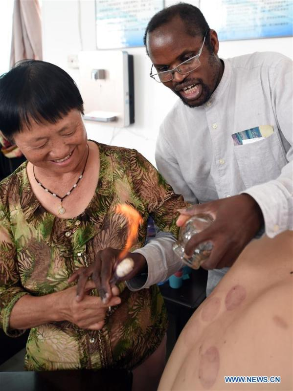 Diarra teaches a local doctor way of cupping at a health center in Kaiyuan City of Hani-Yi Autonomous Prefecture of Honghe, southwest China\'s Yunnan Province, June 6, 2017. (Xinhua/Wang Changshan)