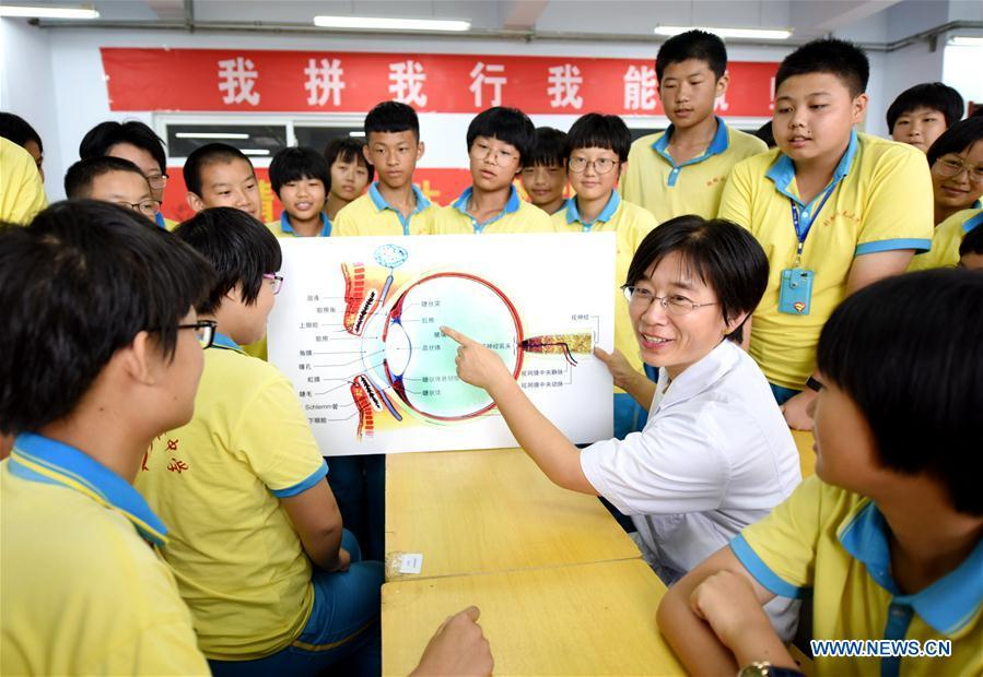 Medical staff illustrates eye care tips at a middle school in Hengshui, north China\'s Hebei Province, Sept. 1, 2018. To cultivate a good habit of using eyes, schools in China prepare eye-care activities for students on the school opening day which falls on Sept. 1. (Xinhua/Zhu Xudong)