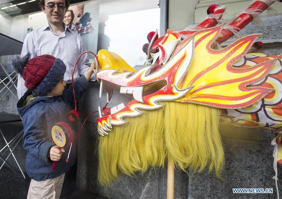 A child touches a dragon head during the \