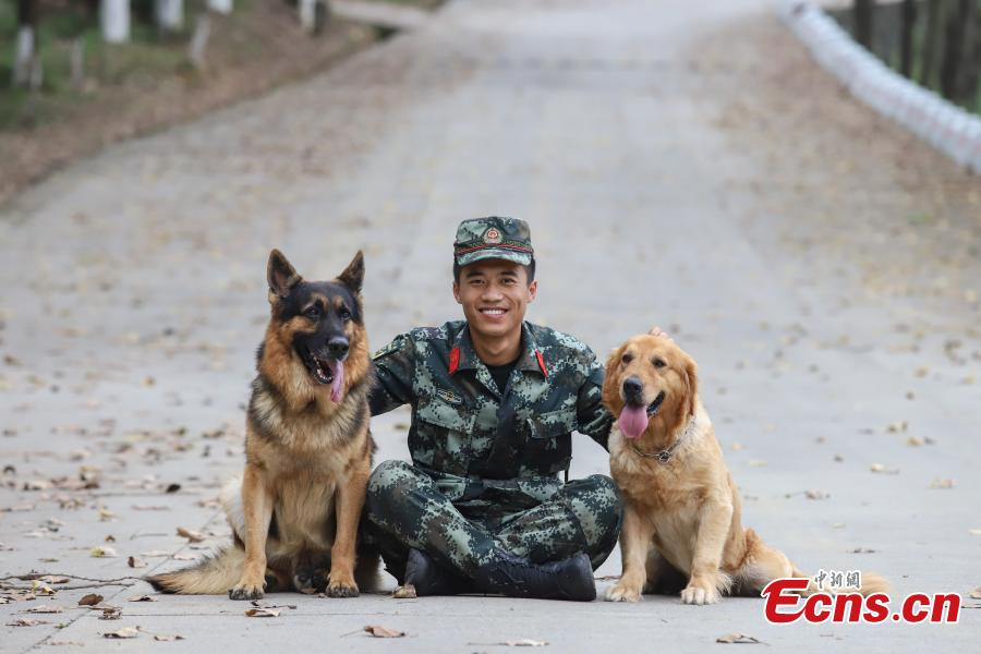 Armed police officer Han Menglin spends his last moments with police dogs he worked with at a training base in Guizhou Province, Aug. 31, 2018. (Photo: China News Service/Qu Honglun)