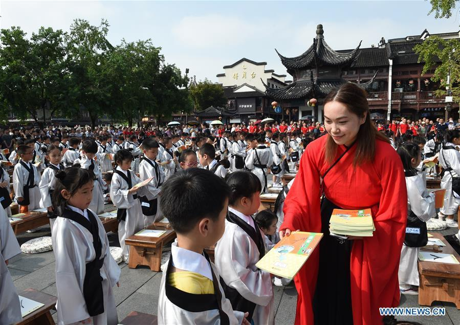 A teacher gives books to children during a first writing ceremony, a traditional education activity for first year students in China, in Nanjing, capital of east China\'s Jiangsu Province, Sept. 2, 2018. (Xinhua/Sun Can)