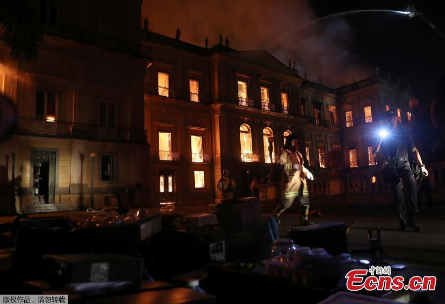 A police officer shines a light at rescued items during a fire at the National Museum of Brazil in Rio de Janeiro, Brazil September 2, 2018. (Photo/Agencies)