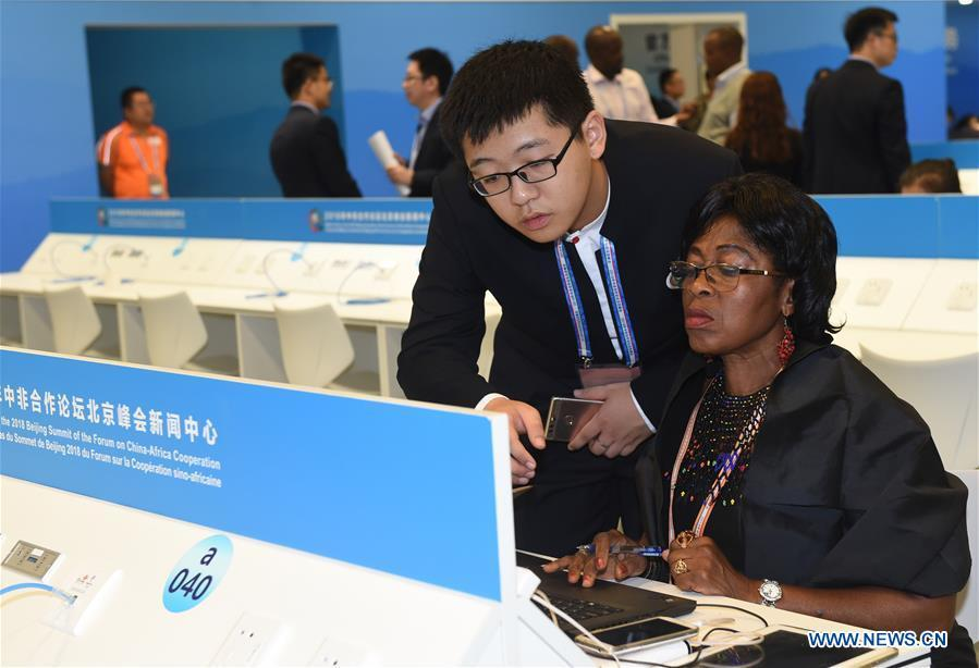 Liu Juncen (L, front), a volunteer from the University of International Business and Economics, provides service to a journalist from Cameroon at the media center for the Beijing Summit of the Forum on China-Africa Cooperation (FOCAC) in Beijing, capital of China, Sept. 3, 2018. The FOCAC Beijing Summit involves some 2,500 volunteers, most of whom are students from 32 higher education institutions. The volunteers are mainly responsible for tasks in venue services, guest reception, registration, media services and transportation. (Xinhua/Luo Xiaoguang)