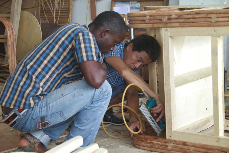 A Chinese carpenter shows a Liberian colleague how to make rattan furniture at a training center in Monrovia, Liberia, on Aug. 20. (Photo/Xinhua)