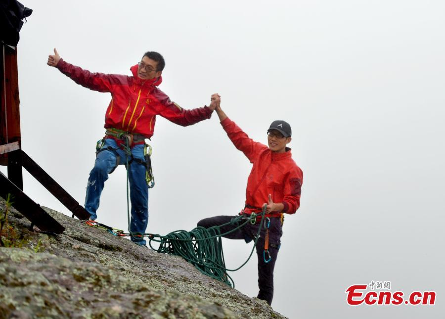 Li Tongxing and Gong Xiuming celebrate after reaching the top in a rock-climbing contest, part of a sports festival in Oroqen Autonomous Banner, North China's Inner Mongolia Autonomous Region, Sept. 3, 2018. (Photo: China News Service/Hou Yupeng)