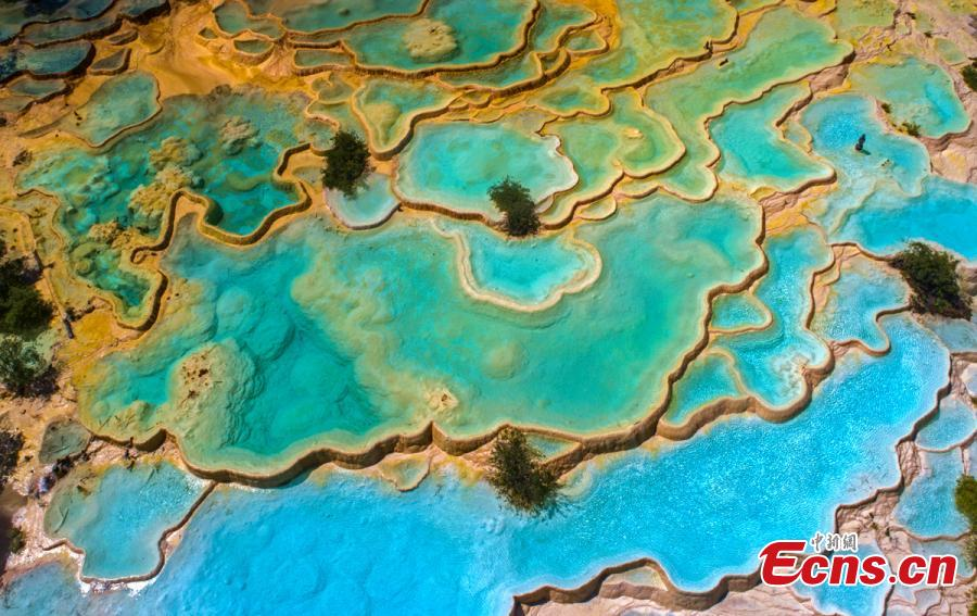 An aerial view of the Huanglong scenic area in Sichuan Province. A UNESCO World Heritage site, the area is known for its colorful pools formed by calcite deposits, especially in Huanglonggou (Yellow Dragon Gully), as well as diverse forest ecosystems, snow-capped peaks, waterfalls and hot springs. The Wucai Pond (Five-Colored Pond) is one of its top attractions. (Photo: China News Service/Yang Jian)