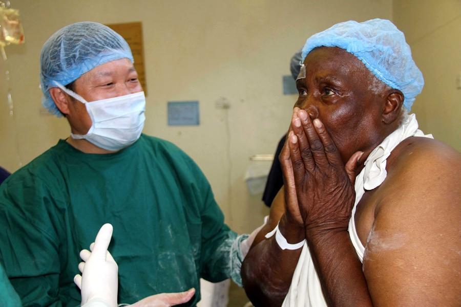 A patient is overwhelmed as his sight is restored after an operation in 2010 at a hospital in Harare, Zimbabwe. Chinese medical teams were sent to Zimbabwe to tackle eye disease. (Photo/Xinhua)