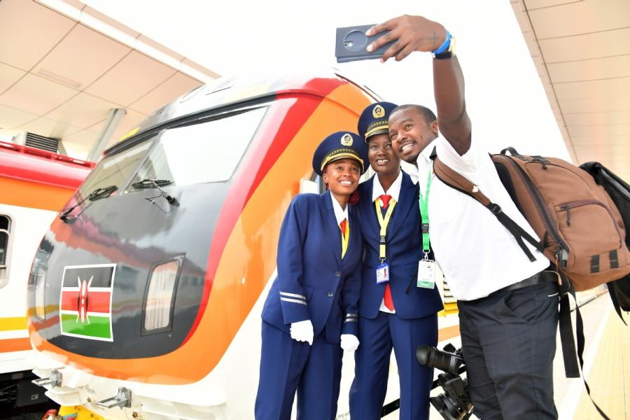 Train staff and a journalist pose for a selfie in Mombasa, Kenya, last year in front of the Madaraka Express train. (Photo/Xinhua)