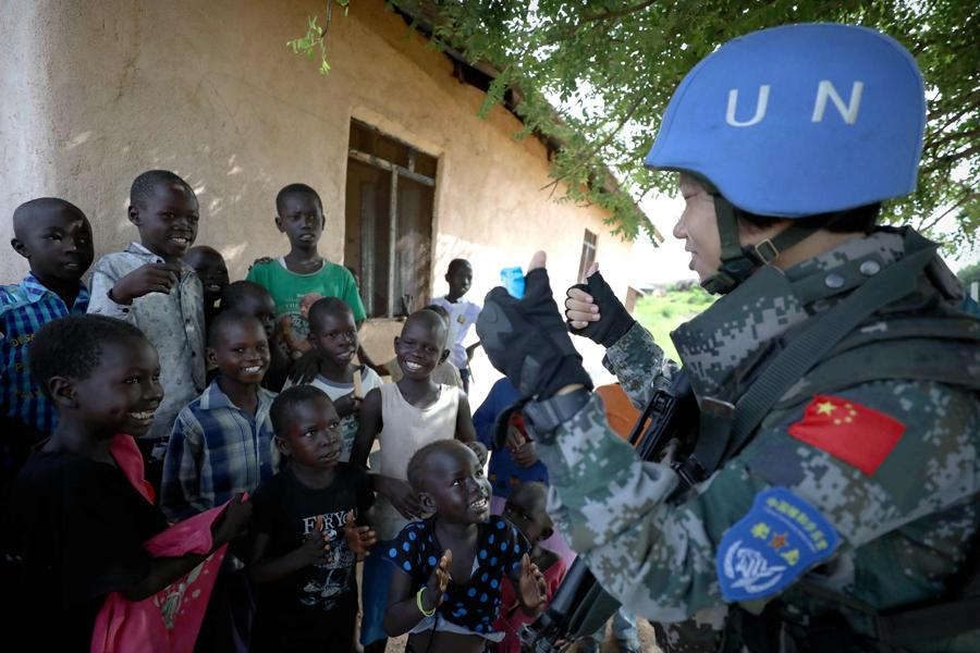 Chinese UN peacekeeper Yu Peijie, 26, sings songs with children in Juba, South Sudan, in April. Yu is the leader of an all-female Chinese peacekeeping battalion in the African country. This year marks the 70th anniversary of United Nations peacekeeping operations and the 28th anniversary of China\'s participation in them. Around 2,500 Chinese peacekeepers are part of UN missions and are involved in activities ranging from minesweeping and road repairs to guarding sensitive installations and providing free clinics. China\'s comprehensive participation in UN peacekeeping operations over the years has earned it deep respect from the rest of the world. (Photo/Xinhua)