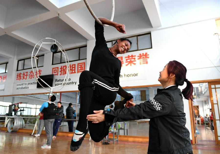 An Ethiopian student has a helping hand from a teacher at Wuqiao Acrobatic Art School in Hebei Province in 2016. (Photo/Xinhua)