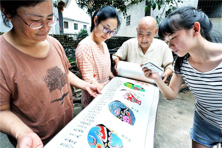 Zhao Xichun shows off his Peking Opera mask scroll in his workshop in Shaorao city, Jiangxi Province on Sept. 2, 2018.  (Photo/Asianewsphoto)