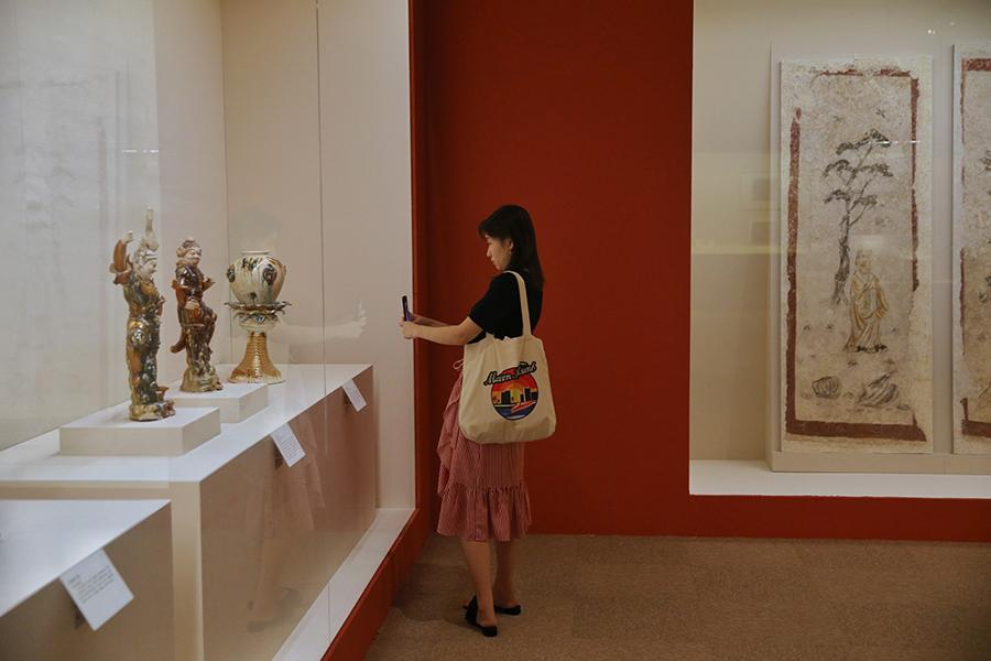 A visitor takes photos of exhibited artifacts. (Photo/China Daily)
