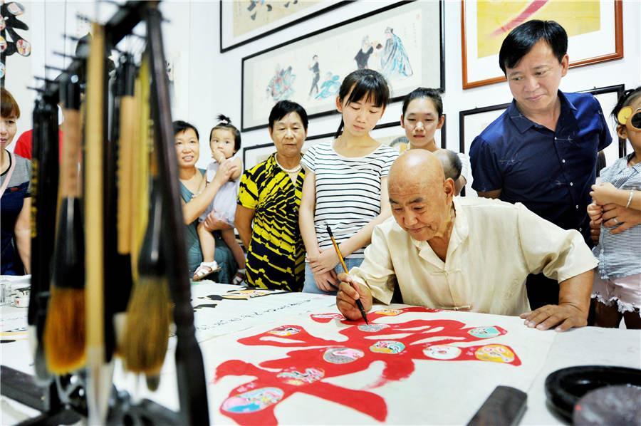 Zhao Xichun works on Peking Opera mask artwork in his workshop in Shaorao city, Jiangxi Province on Sept. 2, 2018. (Photo/Asianewsphoto)