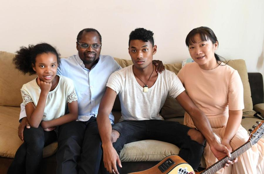 Traditional Chinese medicine practitioner Diarra Boubacar from Mali poses for photo with his wife and two children at home in Kunming, Yunnan Province, on Aug. 28. (Photo/Xinhua)