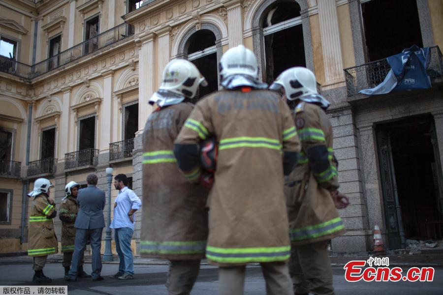Firefighters and Federal Police members talk in front of Rio de Janeiro\'s treasured National Museum, one of Brazil\'s oldest, on September 3, 2018, two days after a massive fire ripped through the building. 