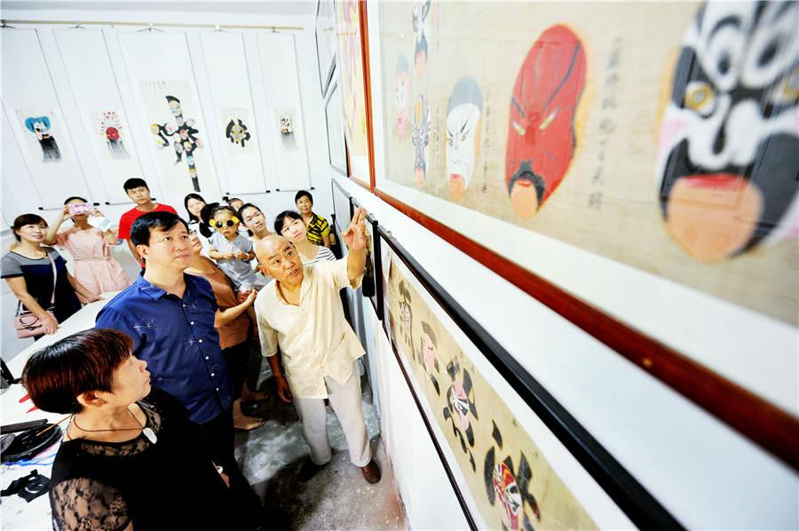 Zhao Xichun introduces his Peking Opera mask scroll in his workshop in Shaorao city, Jiangxi Province on Sept. 2, 2018.  (Photo/Asianewsphoto)