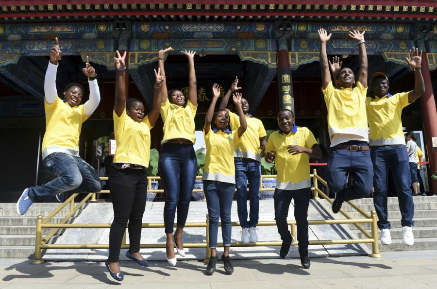 African students, who work as volunteers at Yuanmingyuan, or the Old Summer Palace, jump in unison for a group photo in Beijing on Friday. Yuanmingyuan set up a volunteer recruitment team last year. (Photo/Xinhua)