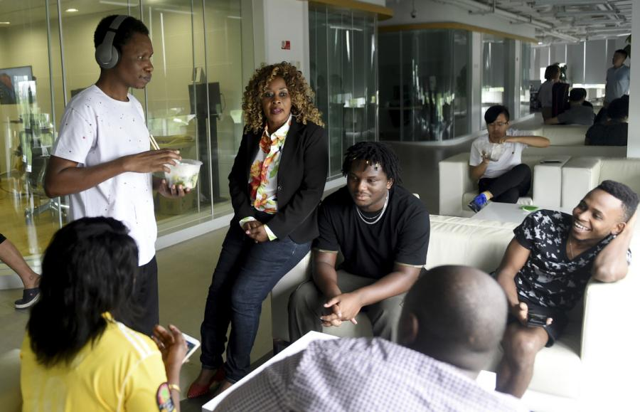 Hilda Malecela, a dubbing specialist from Tanzania, chats with StarTimes Group colleagues in Beijing on Aug. 14. (Photo/Xinhua)