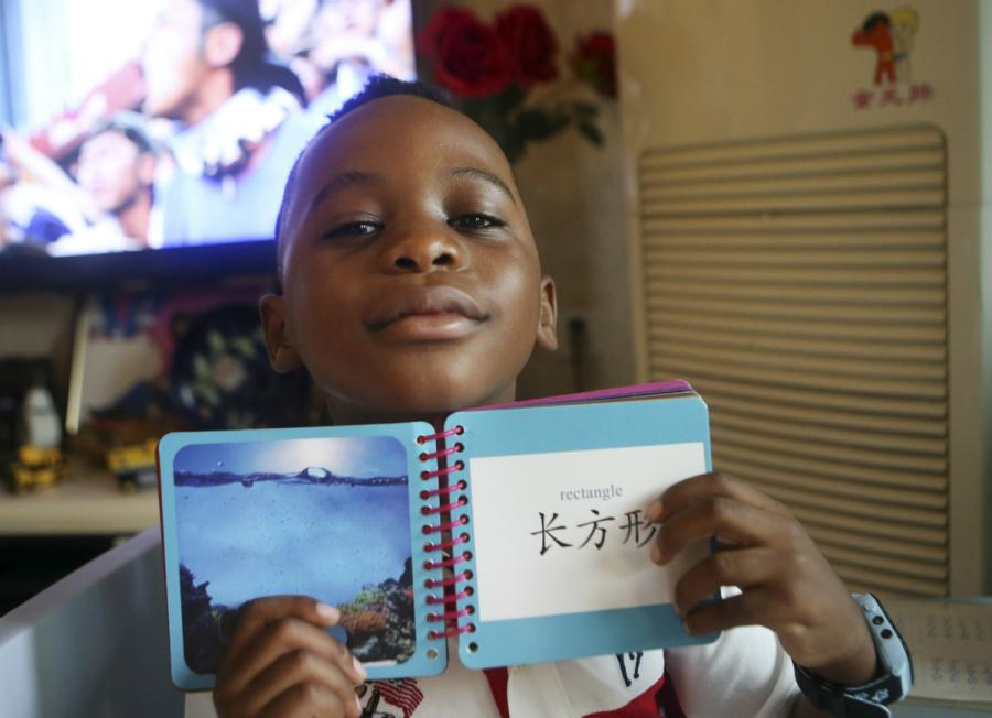 A boy, 6, from Malawi, shows his Chinese character cards at his home in Chengdu, Sichuan Province, in June. (Photo/China Daily)