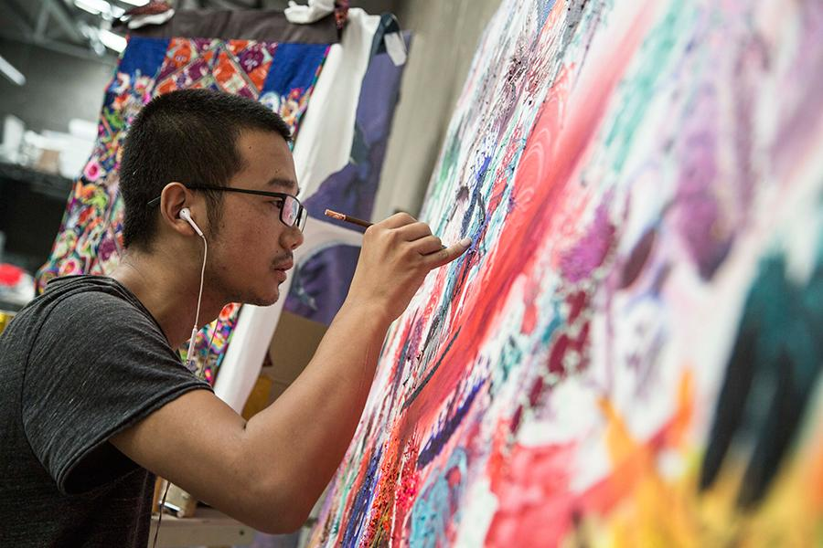 Artist Feng Zhijia works on a painting (Photo provided to China Daily)