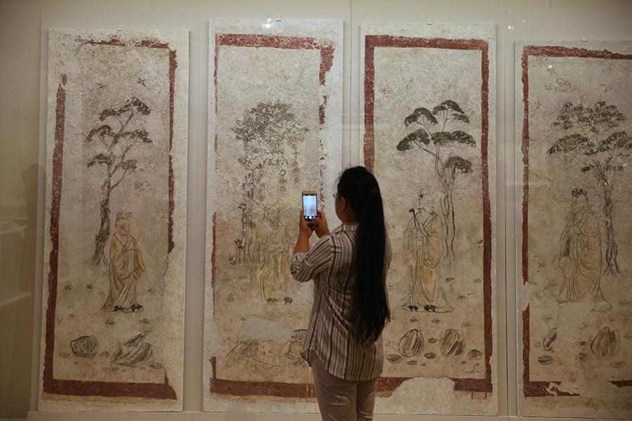 A visitor takes photos of exhibited paintings. (Photo/China Daily)