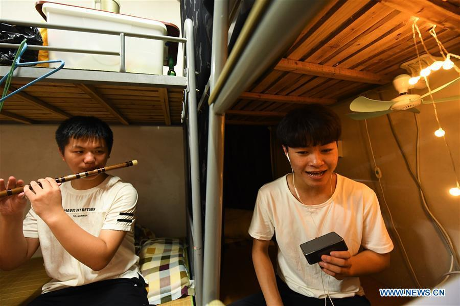 Wang Hongyuan (R) practices singing Yue opera at his dormitory at Shengzhou Yue Opera art school in Shengzhou, east China\'s Zhejiang Province, Sept. 3, 2018. Wang Hongyuan, 17, was born in Taizhou of Zhejiang Province. He is the only male student who learns playing Xiaosheng (role of young man) in Yue Opera at Shengzhou Yue Opera art school. Xiaosheng are usually played by female actresses in Yue Opera which is an old art form originated in Shengzhou and noted for its lyricism and sweet tunes in China. Wang Hongyuan was granted special admission on account of his talent and resolve when he was at second grade in junior middle school. After hard practices, he has already taken part in some performances. (Xinhua/Weng Xinyang)