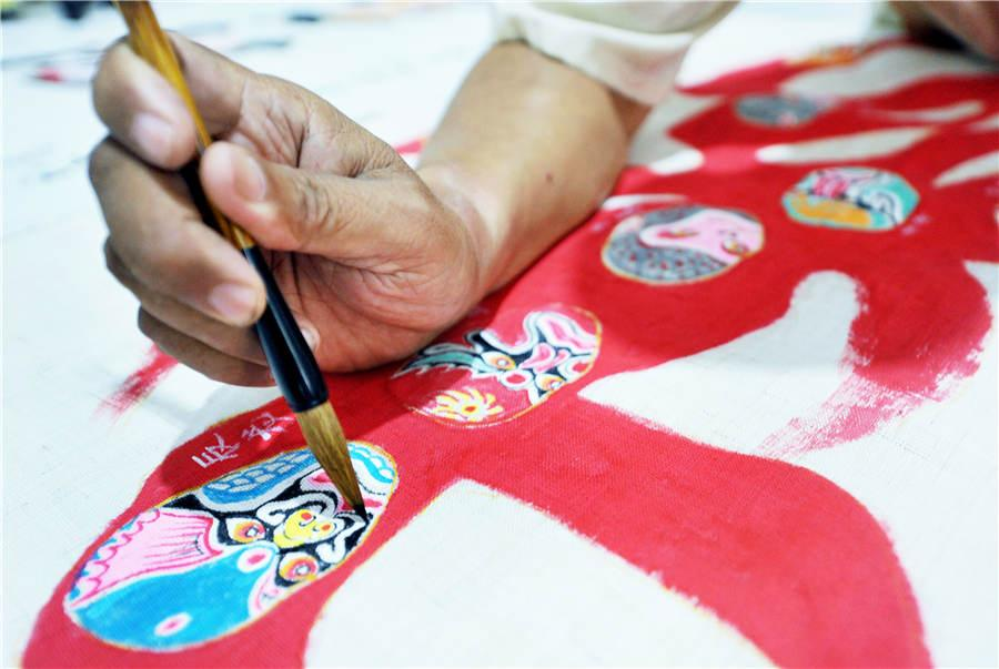 Zhao Xichun works on Peking Opera mask artwork in his workshop in Shaorao city, Jiangxi Province on Sept. 2, 2018. (Photo/Asianewsphoto)  Zhao Xichun, a retired man from Shaorao city in Jiangxi Province, has created a 56-meter-long scroll painted with 288 different Peking Opera masks. This makes it the longest Peking Opera mask scroll nationwide, as the previous record was only 30 meters long.  The scroll, based on figures from classic novels such as Investiture of the Gods, The Romance of the Three Kingdoms, Journey to the West and fairy tales such as \