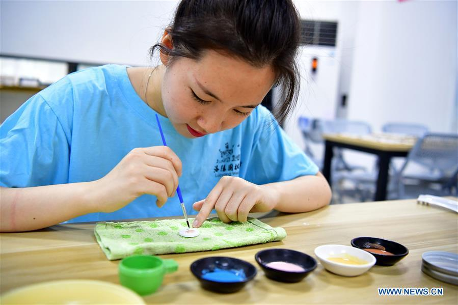 A worker makes a Go piece at Go (Weiqi) museum in Luoyang, central China\'s Henan Province, Sept. 5, 2018. The private museum displays about 25,000 exhibits relating to Go game in China. (Xinhua/Feng Dapeng)