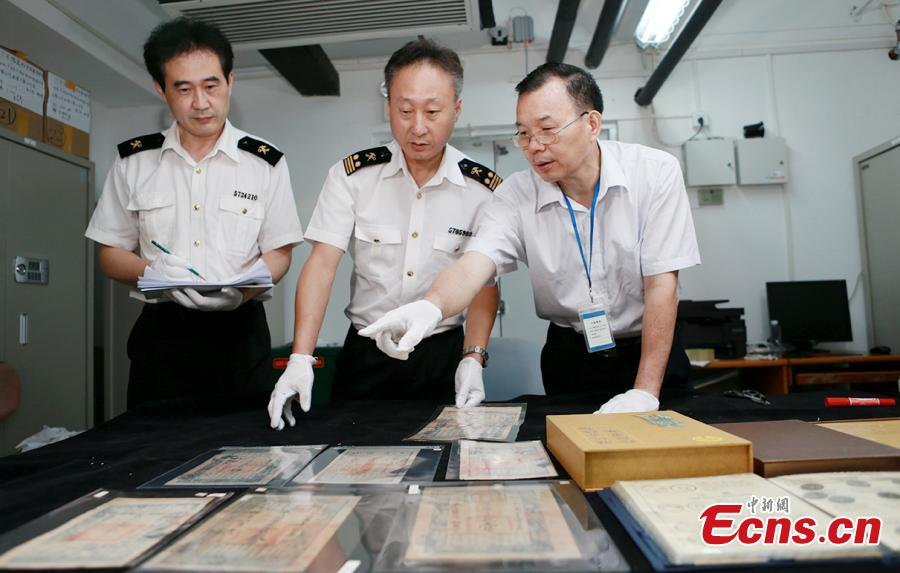 Customs officials show relics found in border checks at a handover ceremony in Guangdong Province, Sept. 6, 2018. Gongbei Customs handed over 157 cultural relics, including currency from the Warring States (475-221 B.C.) and Han Dynasty (206 BC ? 220 AD) periods, to Guangdong Provincial Cultural Relics Bureau. The relics were all Class I items under state protection and forbidden to be taken abroad. Among the findings was a well-preserved account book of the Qing Dynasty (1368-1644), thought to be of great historical value. (Photo: China News Service/Yu Bo)