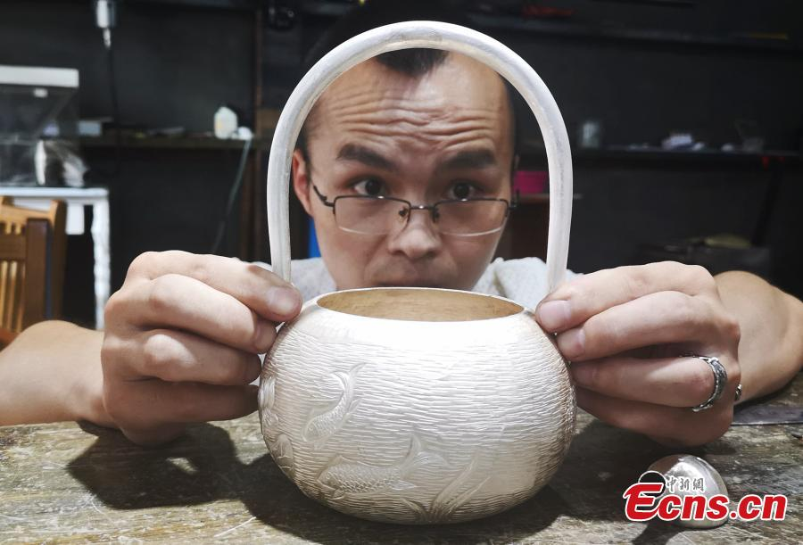 Yang Changgan makes a silver pot in his studio in Zhangjiajie City, Central China's Hunan Province, Sept. 5, 2018. Yang, born in 1986 in Guizhou Province, was exposed to the craft of silverwork from an early age. After completing his bachelor's degree at Nanchang Institute of Technology in 2010, he learned with Yang Guangbin, a master crafter of the silver ornaments of the Miao people. He then opened his own studio in Zhangjiajie in 2015, mainly developing silver pot products. Yang said it takes 10-15 days to make a silver pot as the process involves nearly 100 steps, including pounding, refining and wielding. Yang said his creations sell well in nearly 20 countries and regions. (Photo: China News Service/Wu Yongbing)