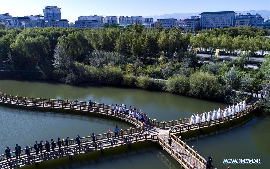 Aerial photo taken on Sept. 7, 2018 shows the group wedding ceremony at a wetland park along the Heihe River in Gaotai County of Zhangye City, northwest China\'s Gansu Province. (Xinhua/Tao Ming)