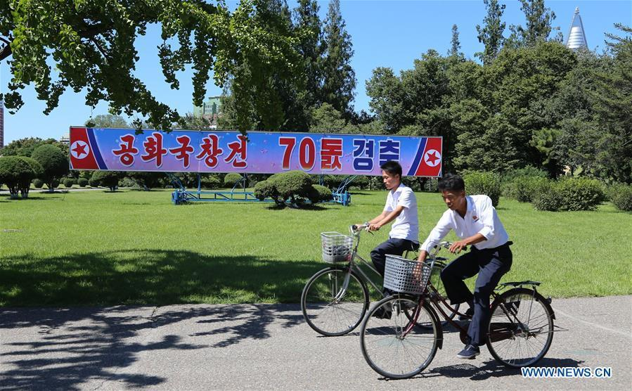 Photo taken on Sept. 8, 2018 shows residents riding pass a poster of National Day celebration in Pyongyang, capital of the Democratic People\'s Republic of Korea (DPRK). Sept. 9, 2018 marks the 70th anniversary of the founding of the DPRK. (Xinhua/Jiang Yaping)