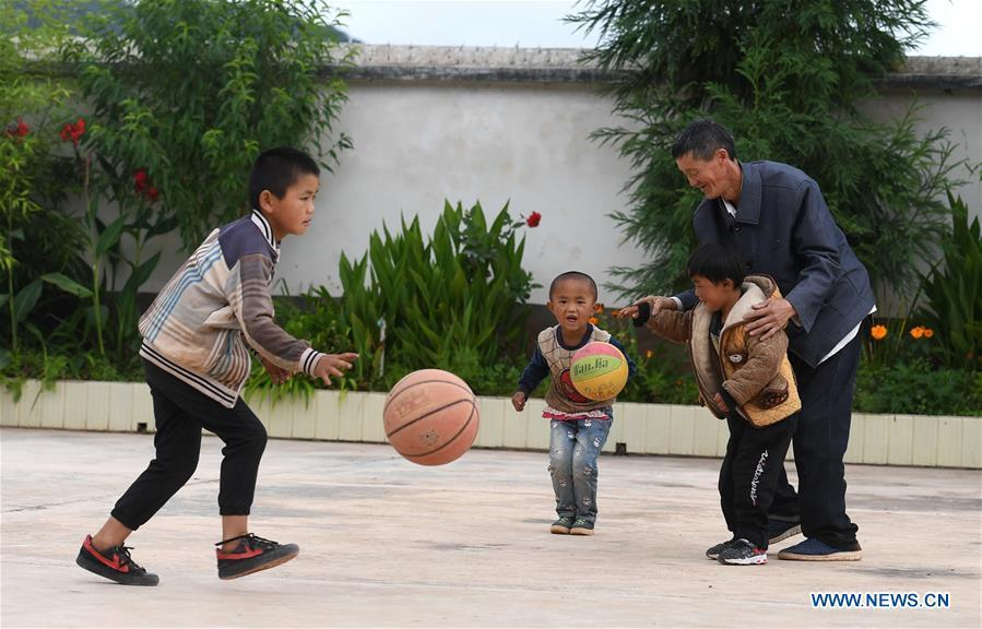 Wang Zhengxiang plays with students at Ayiyang Primary School in Sanmeng Village of Luquan Yi and Miao Autonomous County, southwest China\'s Yunnan Province, Sept. 6, 2018. One teacher, eight students, none was and will be given up thanks to rural teacher Wang Zhengxiang. Wang Zhengxiang of Miao ethnic group, 56, is the only teacher and has been teaching at the remote village primary school of Ayiyang for 38 years. Ayiyang Primary School, lying at an altitude of 2,600 meters above sea level and surrounded by mountains, is not within easy reach of outside world. There are just eight students at the school. Yet Wang takes care of his students with love, consideration and strong sense of responsibility. He buys shoes and daily goods for poverty-stricken students with his own money, and he has tried every means to keep those who wanted to drop out due to economic insufficiency. \